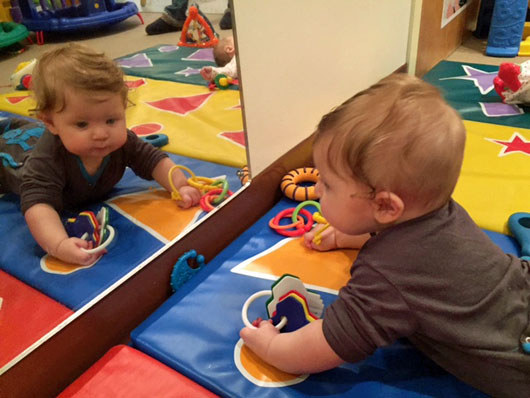 An infant on the floor looking in at his toys in a mirror
