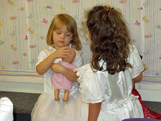 Two pre-Kinders dressed up and playing in the dramatic play area with a baby doll.