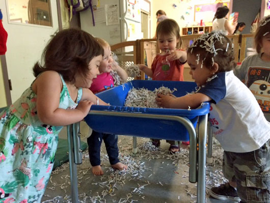 Five preschoolers playing at a water table filled with shredded newspaper