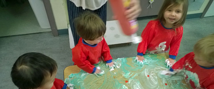 Four preschool children finger painting with shaving cream on a table