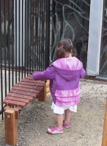 Pre-Kinder child playing with an outdoor xylophone