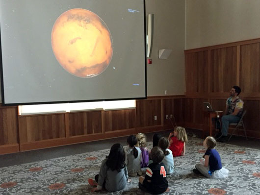 Pre-Kindergarten children looking at a picture of the moon on a big screen