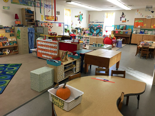 View of a a preschool classroom circle area and center areas with no children